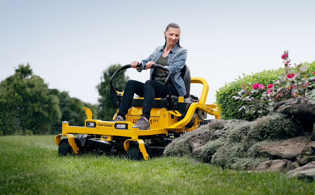woman cutter her lawn with a zero-turn mower
