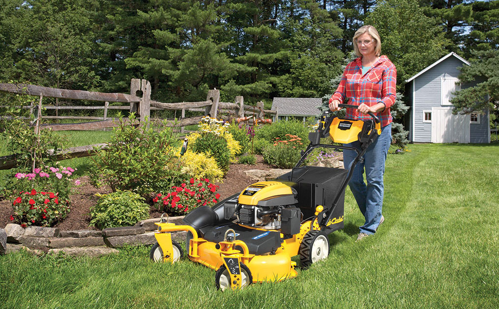 woman mowing in front of her garden bed with a wide-area walk-behind mower