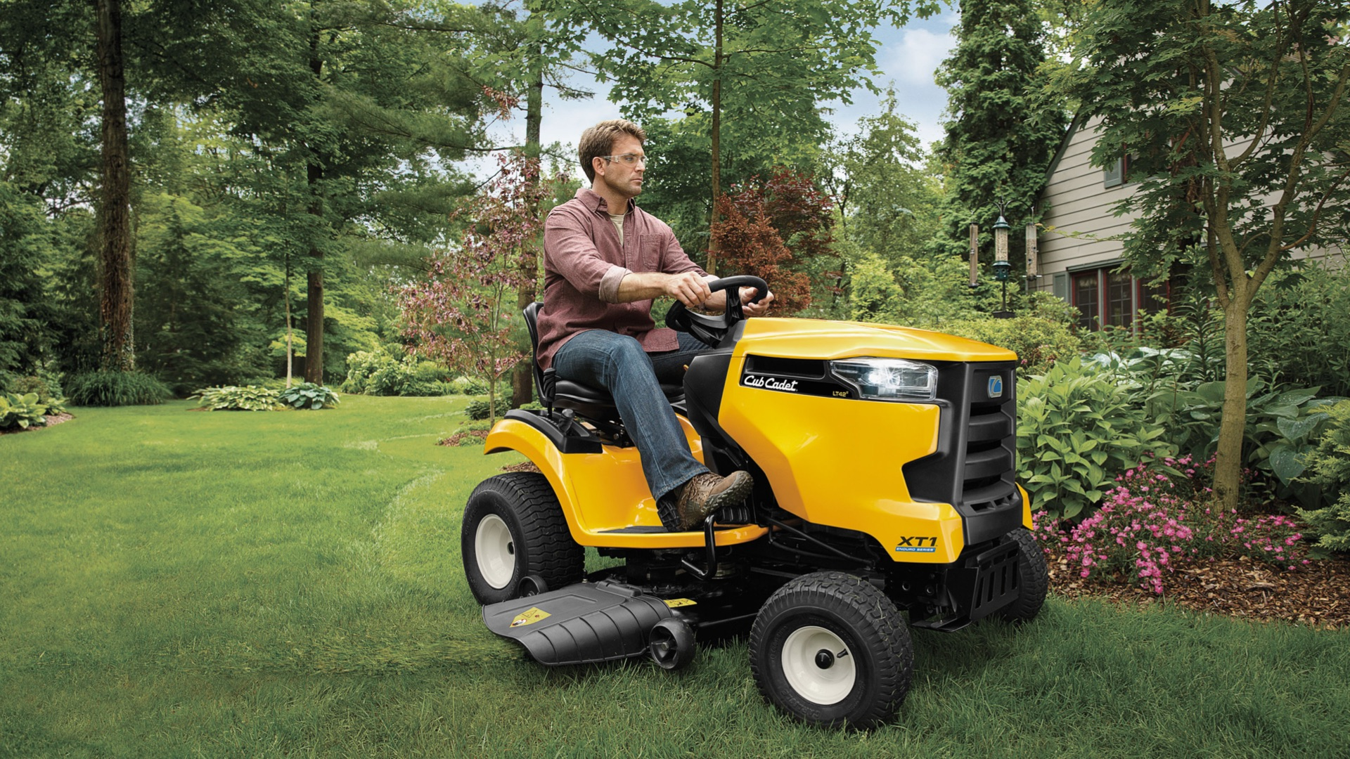 man mowing his yard with a lawn tractor