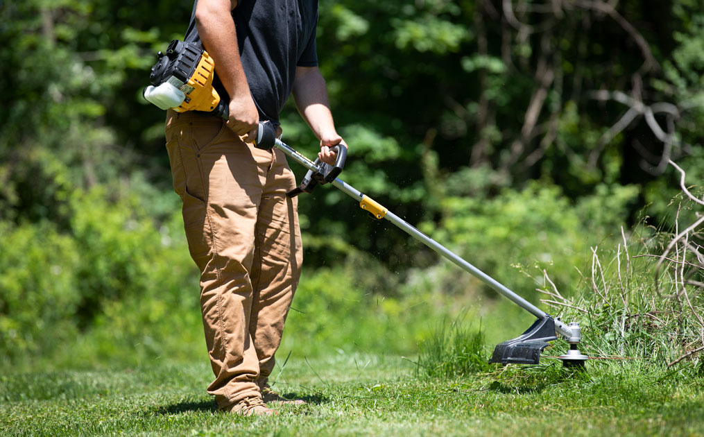 man trimmer grass with weed wacker