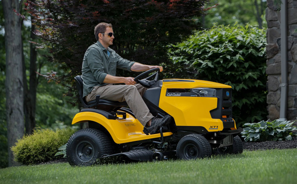 man cutting his grass with an electric riding lawn mower