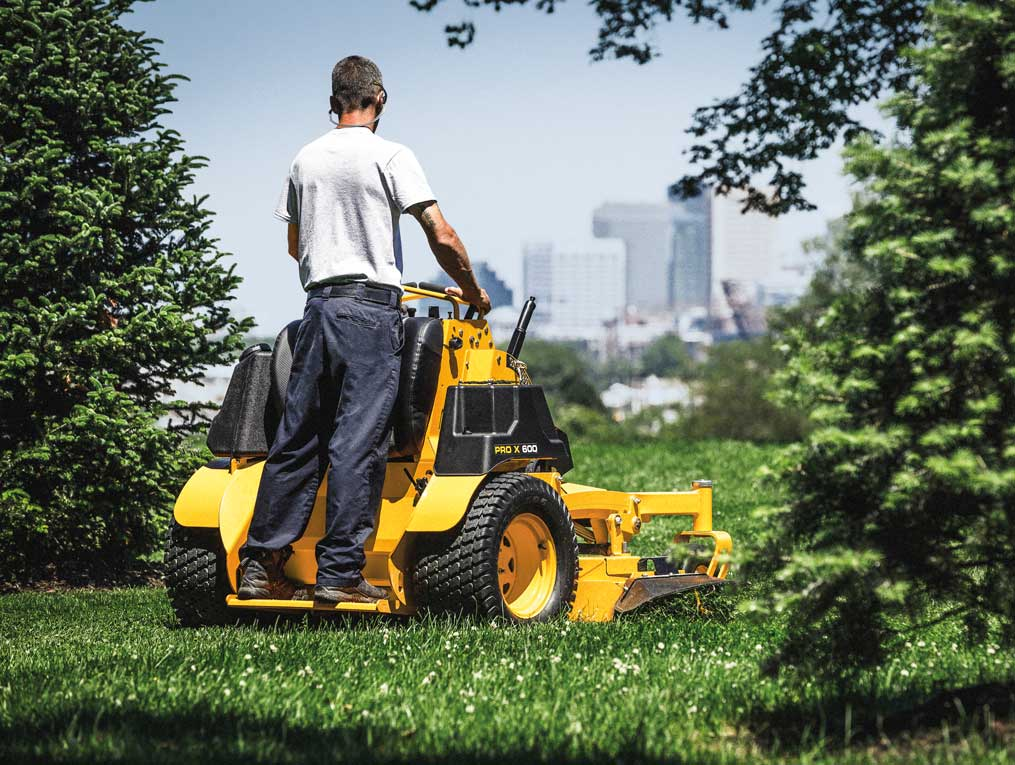 man cutting the grass between pines trees with a commercial stand-on mower