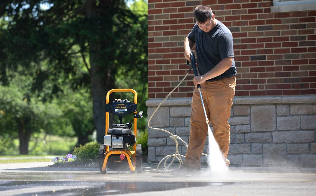 man power washing the driveway