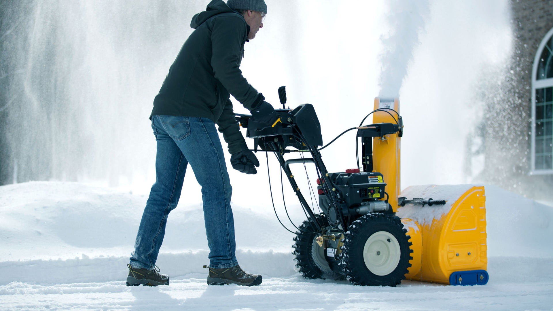 man snow blowing his driving and adjusting the angle of the chute