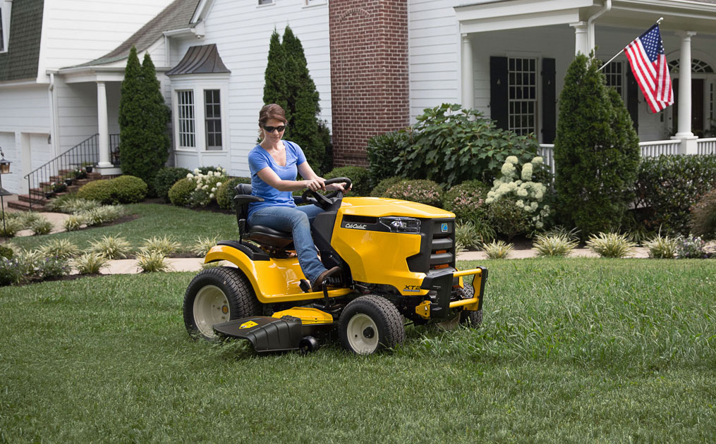 woman mowing the yard with a riding lawn mower