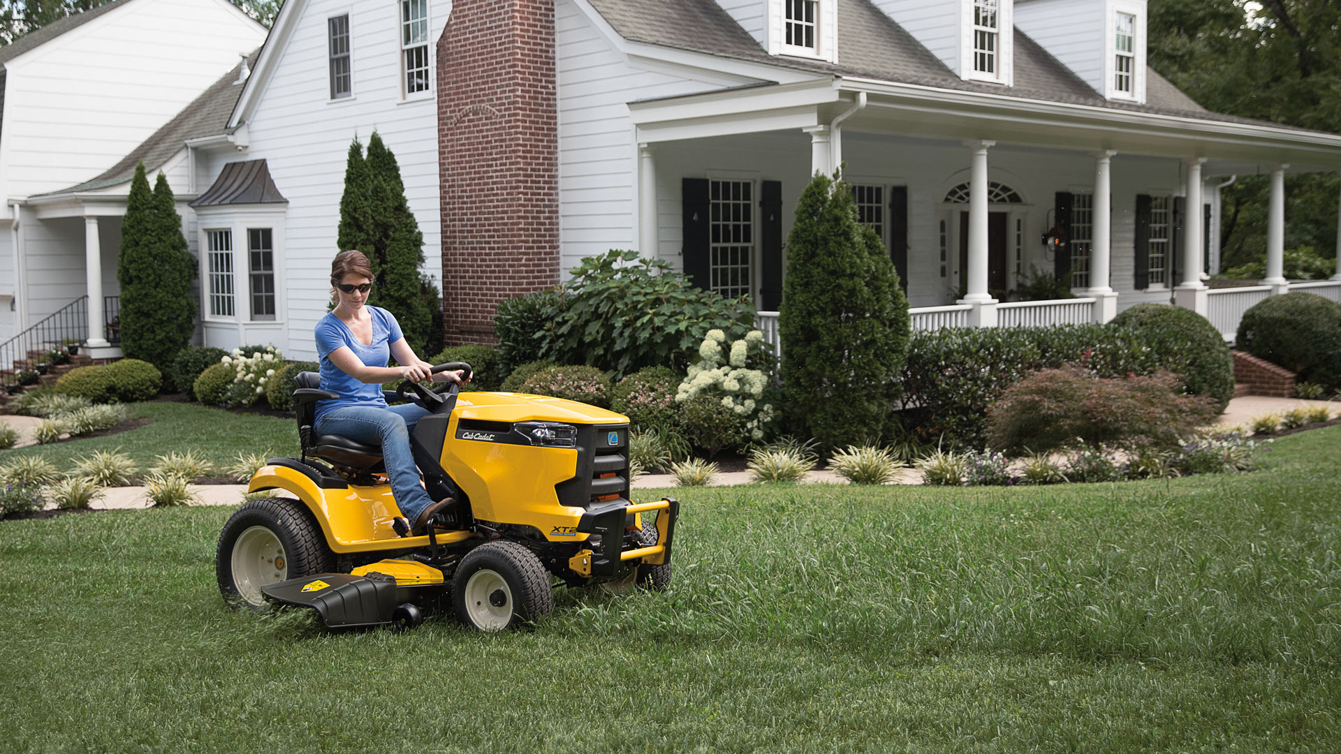 woman mowing her front yard with a lawn tractor