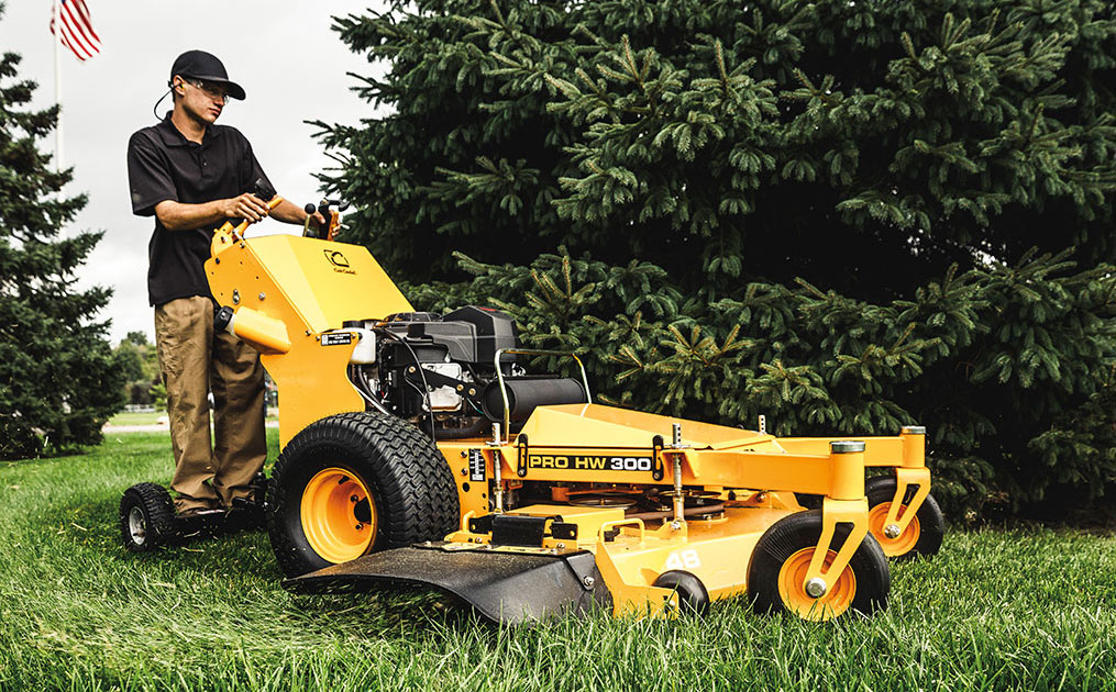 man cutting the grass around a pine tree using a commercial walk-behind mower