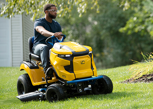 man riding electric mower