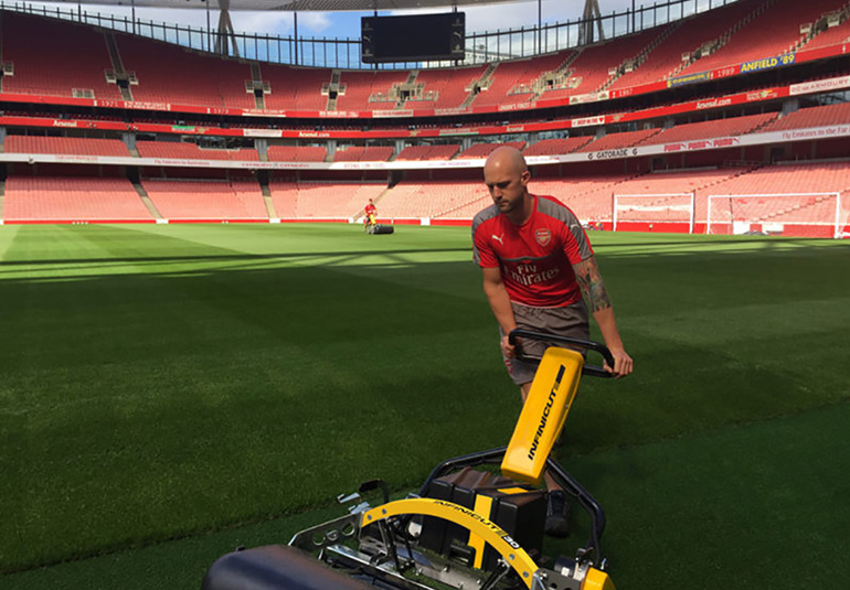 Man mowing soccer stadium with Infinicut commercial mower