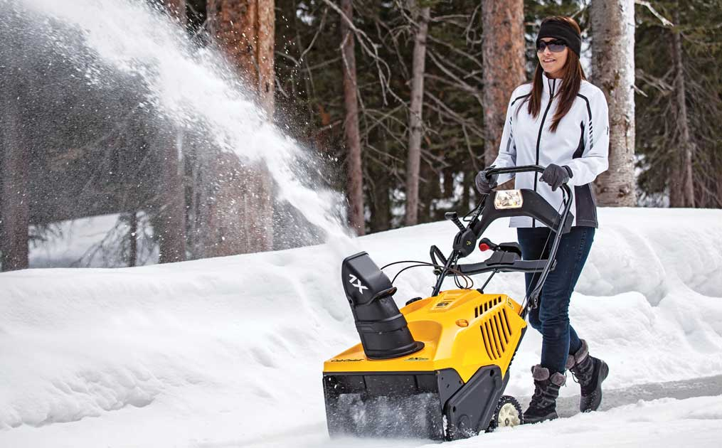 woman snow blowing with 1X single stage snow blower