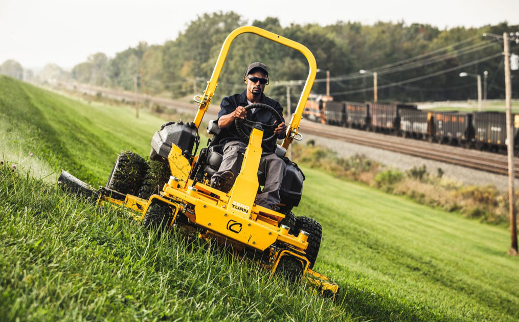 man driving commercial zero turn mower on a slope of a hill