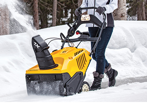 woman snow blower laneway with single Cub Cadet single stage snow blower
