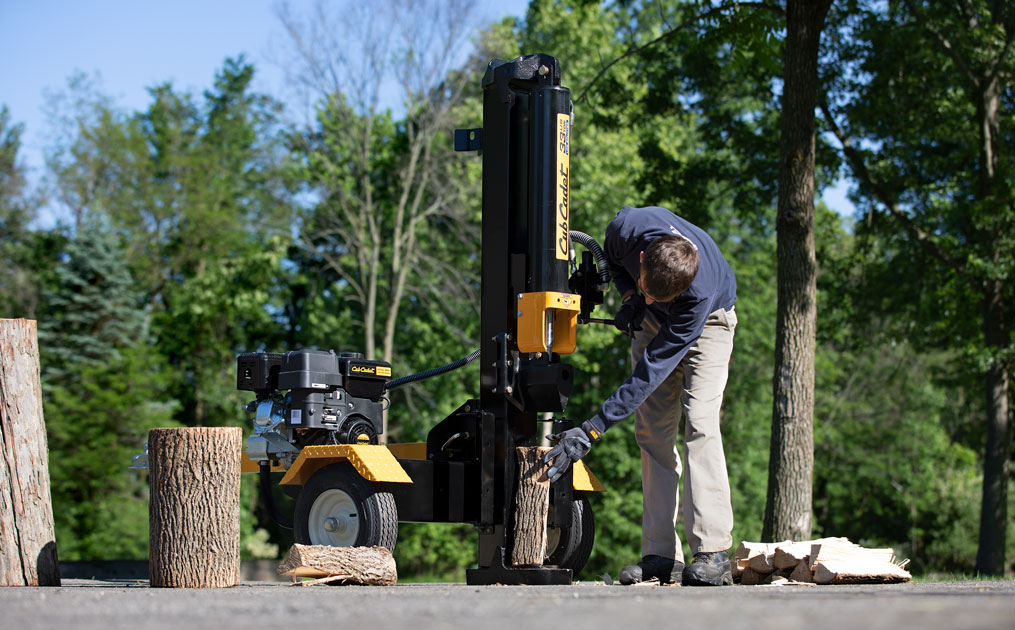 Man using log splitter in wooded area