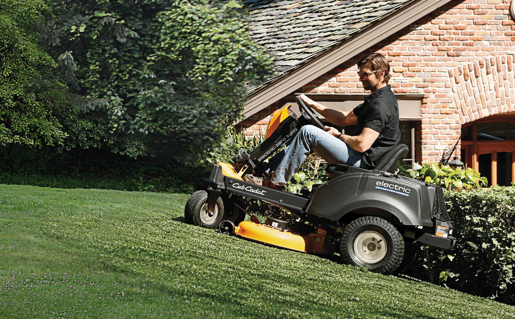 man on electric riding lawn mower cutting his yard