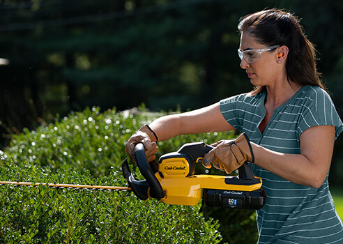 woman using hedge trimmer