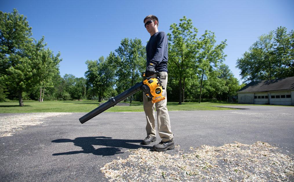 Man using leaf blower on driveway