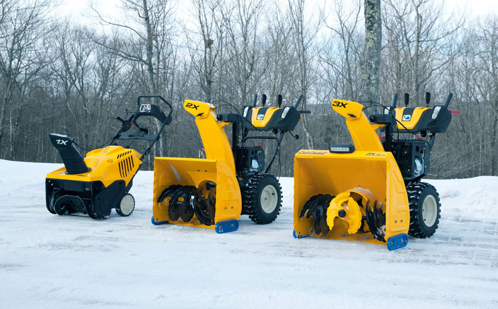 Three Cub Cadet series snow blowers lined up outside on the snow
