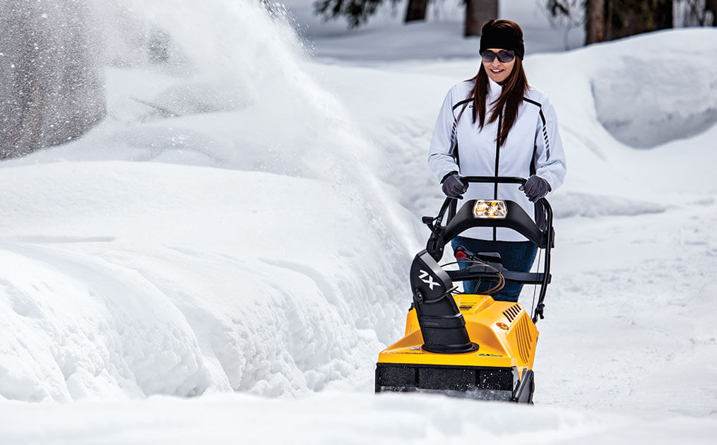 Woman snow blowing her driveway