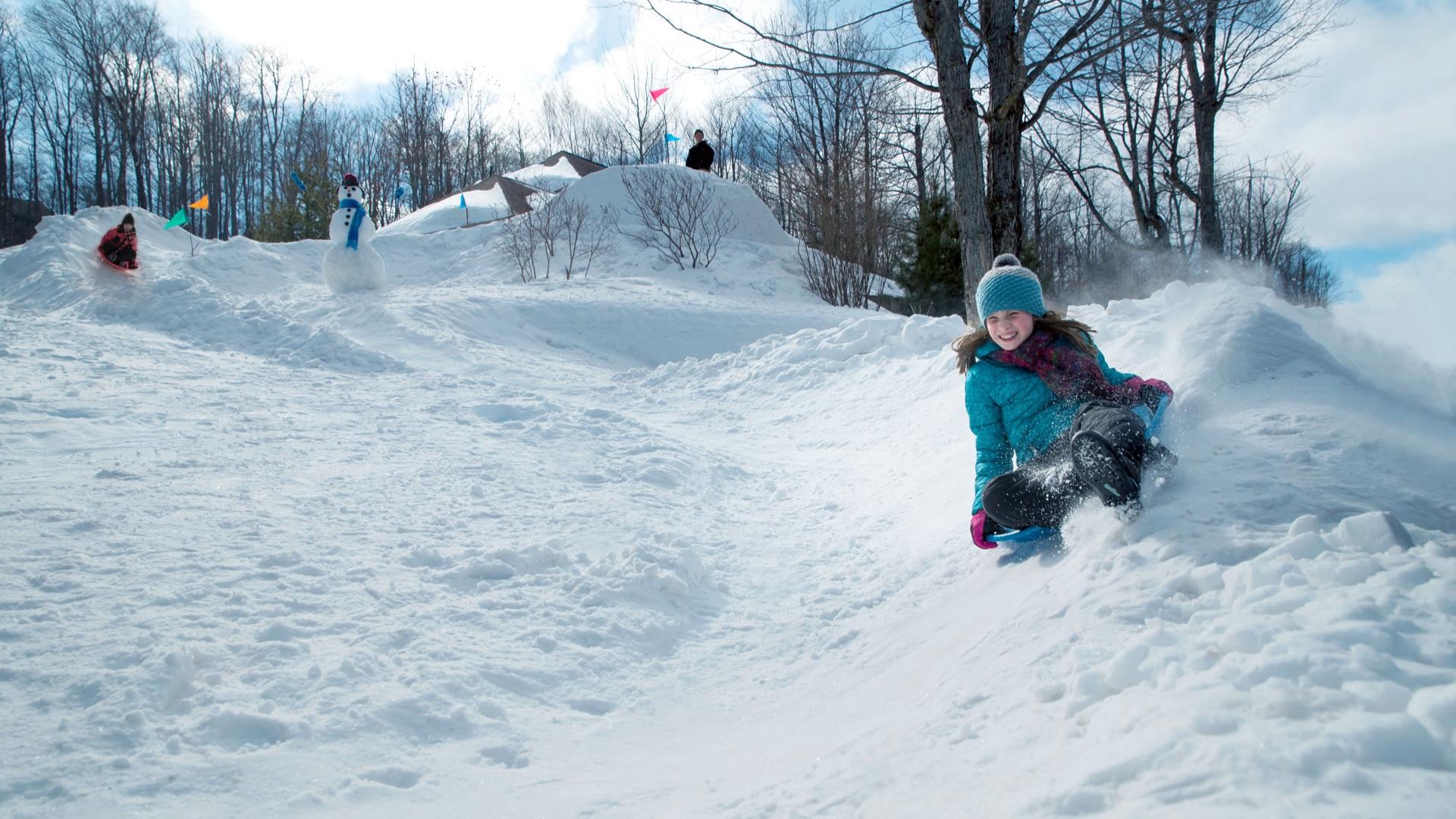 girl sledding down homemade snow track