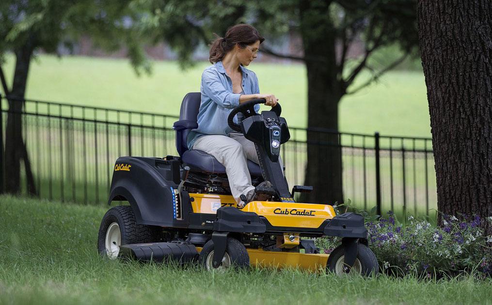 Woman cutting lawn using a zero-turn lawn mower